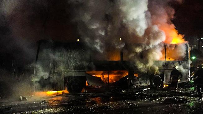 Autobus hořící po útoku na vojenskou kolonu
