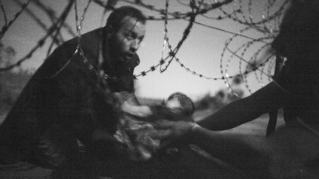 Vítězný snímek letošního ročníku soutěže World Press Photo a zároveň vítěz kategorie Aktualita. Autorem fotografie, na níž otec podává kojence pod ostnatým drátem na srbsko-maďarské hranici je Australan Warren Richardson