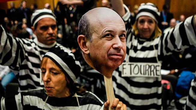 Demonstranti s portrétem Lloyda Blankfeina, šéfa Goldman Sachs