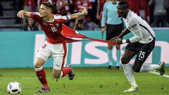 Granit Xhaka byl jedním ze 6 Švýcarů, jimž dres v zápase s Francií praskl. Paul Pogba (vpravo) tomu ale hodně napomohl