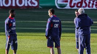 Patrice Evra (vlevo) v diskusi s trenéry (vpravo zády je Raymond Domenech) během hráčské stávky na MS 2010
