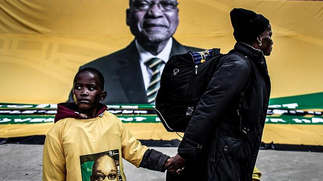 """Volby byly považovány za referendum pro """"problematického"""" prezidenta Jakoba Zumu (na snímku na plakátu v pozadí)"""
