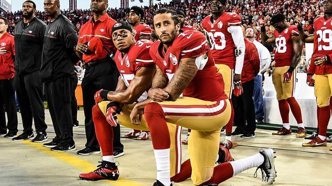 Colin Kaepernick (vlevo) už není při protestu při hymně sám. Přidal se k němu i spoluhráč Eric Reid a hráči v dalších týmech NFL