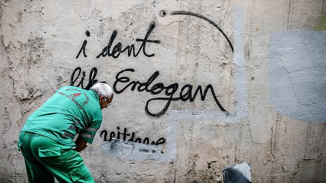 Pracovník úklidové služby přebarvuje nápis proti Erdoganovi