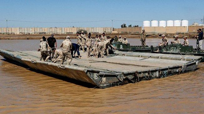 Příslušníci koaličních sil a iráčtí vojáci na plovoucím mostu přes Tigris
