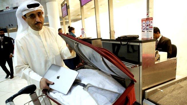 Kuvajtský aktivista Thamer al-Dakheel Bourashed ukládá svůj notebook do zavazadla směřujícího do zavazadlového prostoru. Bourashed patří mezi odpůrce nového nařízení, považuje jej za nesmyslné