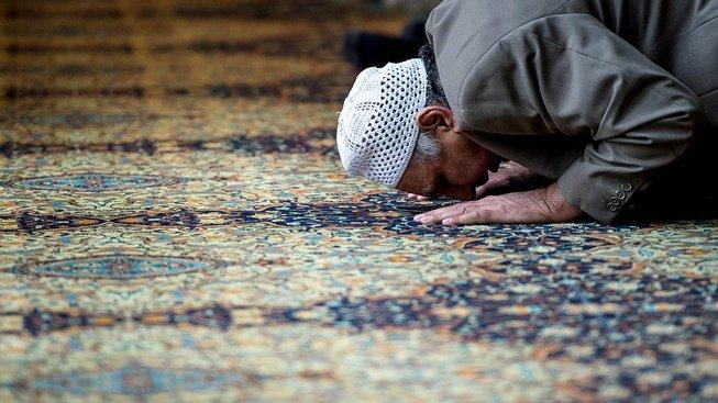 Muž modlící se v centrální mešitě v Manchesteru