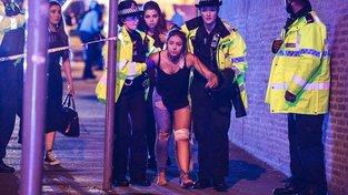 Jedna ze zraněných, kterou odvádějí pryč policisté