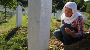 Jedna z pozůstalých modlící se u hrobu svého bratra v pamětním centru nedaleko Srebrenici