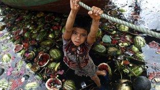 Místní chudina hledá ve špinavé a znečištěné řece jídlo, například vyhozené melouny
