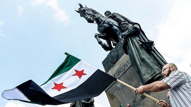 Protestující se syrskou vlajkou na Václavském náměstí