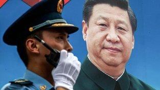 Čínský prezident Si-ťin-Pching (na plakátu) se podle některých chystá udržet u moci i po roce 2022