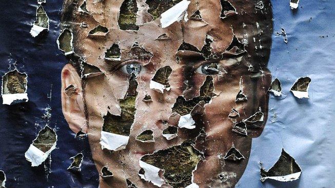 Poničený plakát s Macronem