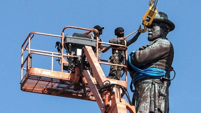 Maskovaní dělníci odstraňují sochu generála Roberta E. Leeho v New Orleans
