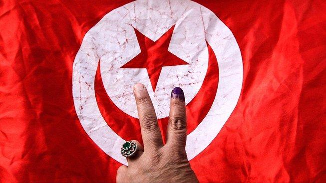Tunisanka ukazuje prst od inkoustu poté, co odvolila v parlamentních volbách před třemi lety