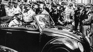 Ferdinand Porche (bez klobouku stojící vedle auta) se v cestě za úspěchem neštítil ani spolupráce s nacistickým režimem. Na snímku Adolf Hitler v Brouku, který pro něj Porsche navrhl