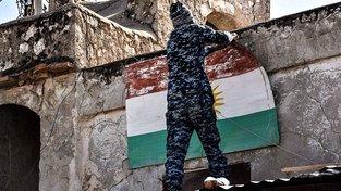 Irácký bojovník strhává kurdskou vlajku v Kirkúku