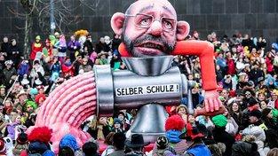 Alegorický vůz na německém karnevalu zobrazuje Martina Schulze, který se odrovnal vlastní vinou