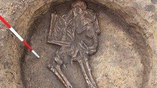 V neobvykle upraveném hrobě objímá žena malé dítě