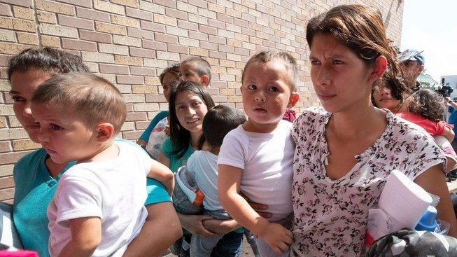 Matky s dětmi, dopadené při přechodu hranice z Mexika do Spojených států míří v texaském McAllenu k autobusům, které je odvezou k příbuzným do amerického vnitrozemí. Po nařízení Donalda Trumpa, které zakázalo oddělovat děti migrantů od rodin, dostaly sledovací náramky a azylové řízení podstoupí na svobodě.