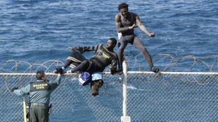 Afričané přelézají hraniční plot ve španělské enklávě Ceuta na severu černého kontinentu. Španělský pohraničník se jim v cestě do Evropy snaží zabránit