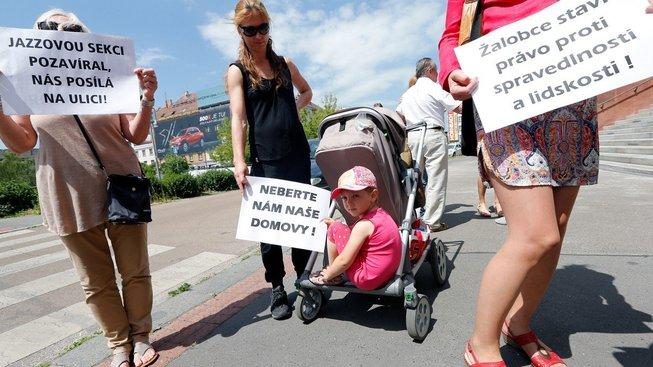 Protestující klienti H-systemu. Jeden z plakátů upozorňuje na konkurzního správce Josefa Monsporta, který v době komunistického režimu pracoval jako prokurátor a podílel se na pronásledování členů Jazzové sekce