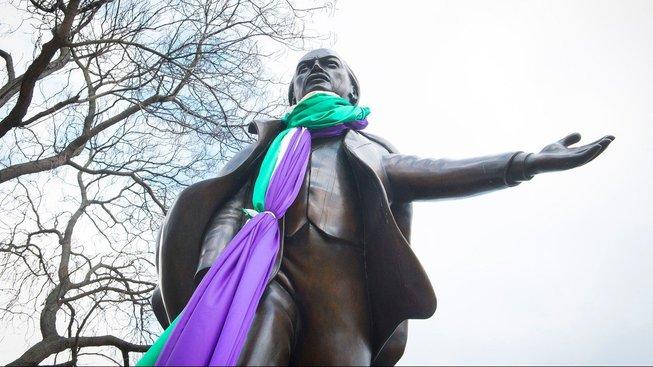 Socha Davida Lloyda George s vlajkou sufražetek kolem krku.
