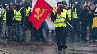Komunista drží vlajku se srpem a kladivem během protestu žlutých vest v Paříži. Srp a kladivo si ponechal ve znaku také český Komunistický svaz mládeže, který s třešničkáři z KSČM patří ke svolavatelům protestu žlutých vest na Václavském náměstí