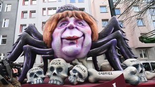 Angela Merkelová jako černá vdova na karnevalu v Düsseldorfu