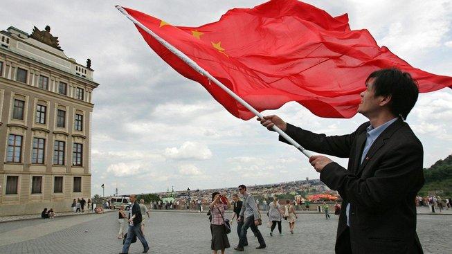 Číňan mává vlajkou před Pražským hradem. Dobyté území?