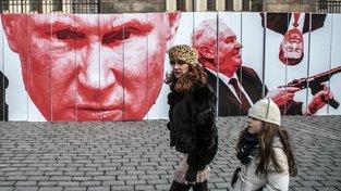 Matka s dcerou procházejí kolem plakátu se snímky prezidentů Miloše Zemana (likvidujícího novináře) a Vladimira Putina vyvěšeném na plotu Pražského hradu členy skupiny Kaputin