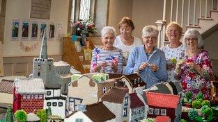 Skupina sedmi pletoucích babiček vytvořila model jejich vesnice, na kterém nechybí ikonické stavby, ale ani pošta, obchůdky a množství detailů. Na snímku zleva Sue Cottisová (68), Jeanette Wilsonová (70), Carolyn Ystenesová (70), Margaret Baughanová (73), Sue Couvesová (64) a Sue Pringleová (70)