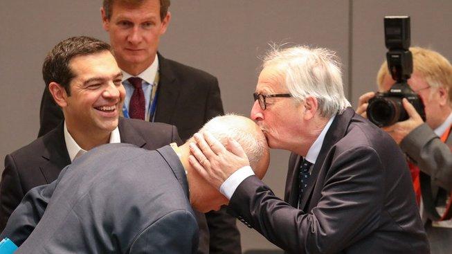 Jean-Claude Juncker líbá na pleš místopředsedu komise Franse Timmermanse. V pozadí (s hustou kšticí) se směje řecký premiér Alexis Tsipras