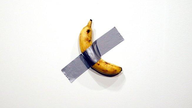Cattelanův banán přilepený na zdi stříbrnou páskou