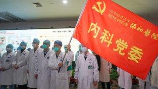 Zdravotníci z města Wu-chan skládají přísahu na rudou vlajku se srpem a kladivem