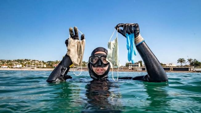 Potápěč s kořistí - rouškami a gumovou rukavicí. Na Azurovém pobřeží zůstala po koroně spoušť