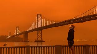 Muž zírající na oranžové nebe pod mostem Oakland Bay, který se klene přes Sanfranciský záliv.